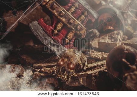 Medieval battlefield in the stone cave. Focus point on the skull with glowing eyes.