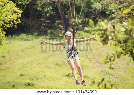 Happy woman riding a zip line in a lush tropical forest