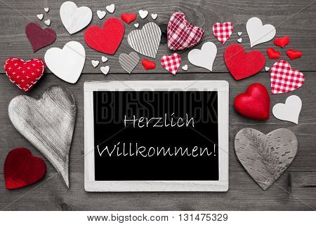 Chalkboard With German Text Herzlich Willkommen Means Welcome. Red Textile Hearts. Grey Wooden Background With Vintage, Or Retro Style. Black And White Style With Colored Hot Spots
