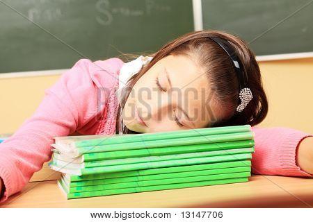 Educational theme: schoolgirl sleeping on her textbooks in a classroom.