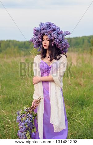 Beautiful young girl in a lilac dress with a wreath of lilac in the field.