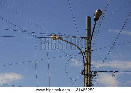 Lamp post with many cables that run in different directions. Electrical wire on pole. chaotic wire with nest on pole and blue sky background