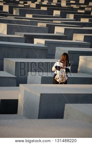 BERLIN, GERMANY - MAY 10: A tourist stands between the gray concrete blocks of the Monument to the Murdered Jews of Europe on May 10, 2016 in Berlin.