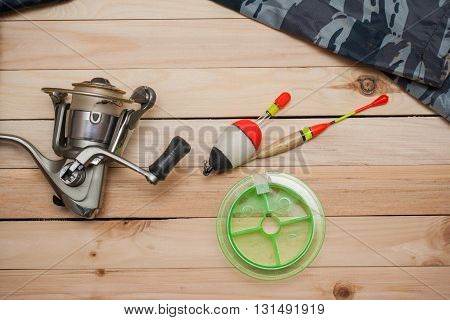 Set for fishing on the wooden background with camouflage clothing. Coil colored floats fishing line. Fishing and recreation.