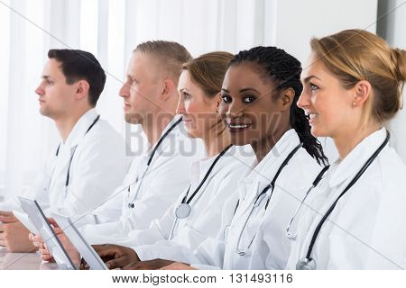 Group Of Doctors In Labcoat Using Laptop At Desk