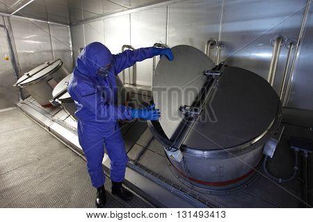 Technician in mask, blue uniform checking technological system n high tech environment