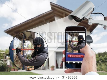 Person Hand Holding Mobile Phone Detecting Burglar In Security System With Surveillance Camera Behind poster