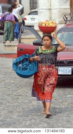 ANTIGUA GUATEMALA MAY 02 2016: Portrait of a Mayan woman carring fruits on her head. The Mayan people still make up a majority of the population in Guatemala,