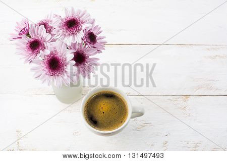 Coffee mug and lilac daisies top view. Coffee cup. Strong coffee. Coffee mug. Morning coffee. Cup of coffee. Coffee break.