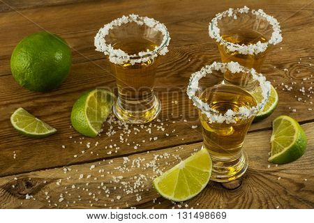 Gold tequila shots on the rustic wooden table. Tequila. Gold Mexican tequila. Tequila shot. Alcohol drink