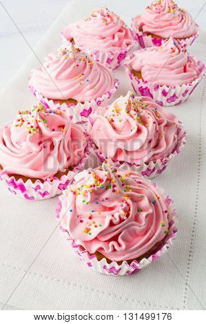 Pink cupcakes on the linen napkin. Birthday cupcakes. Homemade cupcake. Sweet cupcake. Gourmet cupcakes. Sweet pastry. Sweet dessert.