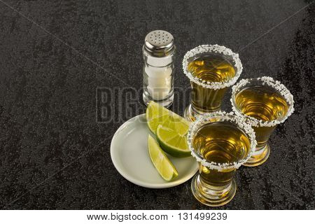 Tequila shots with lime on black background. Alcohol drink. Gold Mexican tequila. Tequila shot. Tequila.