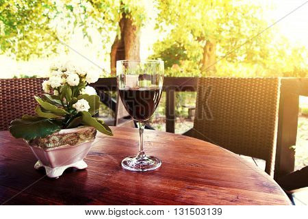 Red whine on the table in idyllic courtyard in restaurant at summer. Drink concept.