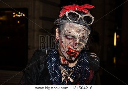 Bologna, Italy - May 21, 2016: Bologna zombie apocalypse walk. Close up of the face of a rotten, bloody and terrifying zombie.