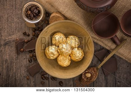 Italian chocolate sweets Ferrero Rocher with Chinese tea set on the wooden table