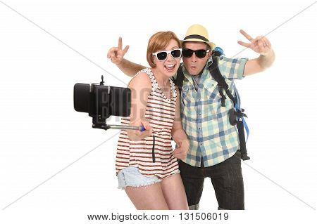 young attractive American couple taking selfie photo portrait together with mobile phone and stick isolated on white background wearing tourist backpack chic hat and sunglasses in trendy look
