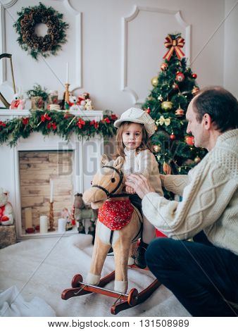 Old grandfather and granddaughter with toy horse near Christmas tree
