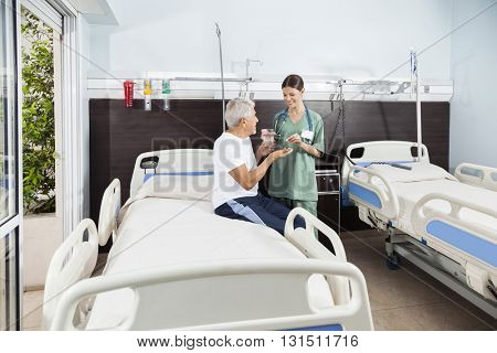 Nurse Giving Medicine And Water To Patient In Rehabilitation Cen