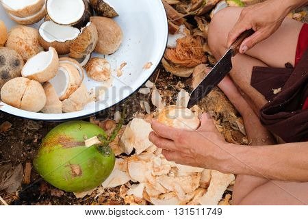 Stripping coconut with a knife, fresh fruit