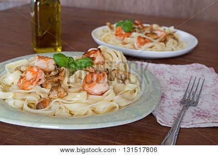 Fettuccini pasta in cream sauce with shrimp and mussels. decorated basil leaves