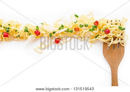 Instant noodle and wooden fork spicy onion onion leaf with copyspace for web banner.