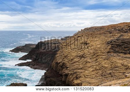 People walking on volcanic rocky promontory at blowholes, Cape Bridgewater in Victoria, Australia