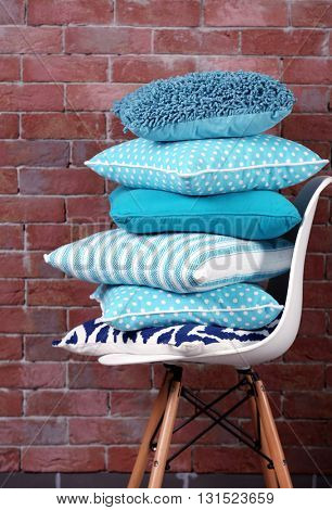 Few pillows on chair against brick wall background