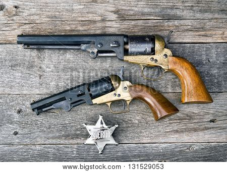 The guns that won the west and silver sheriff badge.