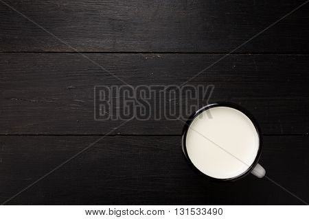 Black weathered wooden board with white tin cup with milk as image background with copy-space.