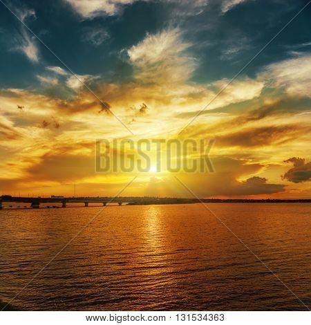 orange sunset over river in dramatic sky