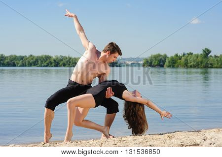 Contemporary dance. Man and woman in passionate dance pose on beach. Young couple dancing modern dance in beautiful pose outdoors. A man with naked torso on sand. Sky and water river in background.