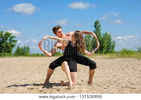 Contemporary dance. Man and woman in passionate dance pose on beach. Young couple dancing modern dance outdoors. Man and woman hands showing infinity symbol. Man with naked torso on sand.