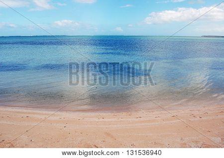 Mirror like water surface on mauritian sandy quite beach