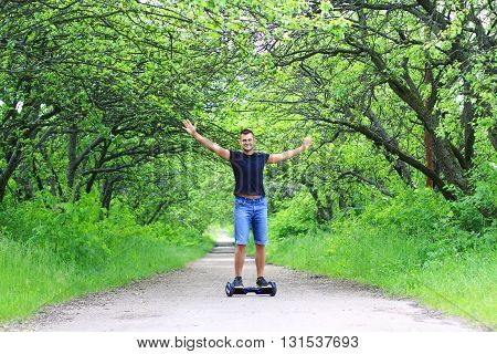 young fit man riding an electrical scooter outdoor - portable personal eco transport, gyro scooter, gyroboard, smart balance wheel, hoverboard