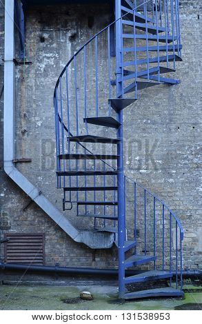 Blue outdoor spiral staircase in front of a brick wall with water tubes.