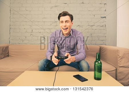 Excited  Man Sitting On Sofa With Bottle Of Beer And Playing Video Games