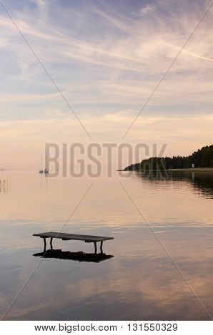 Bench in the water on sunset and sailboat near horizon