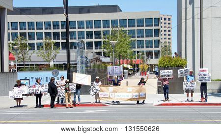 San Jose CA - May 26 2016: Unidentified protestors hold signs across from the entrance to the Hillary Clinton political rally. Radio broadcast journalist from station 94.1 KPFA interviews protestors