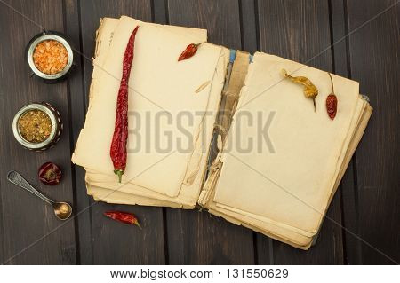 Recipe book and vegetables. Chili pepper and tomatoes. Food preparation according to the old recipe book. Grandma's recipe book. Old recipes for cooking.