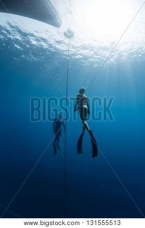 Two freedivers ascending from the depth using fins. Constant weight discipline