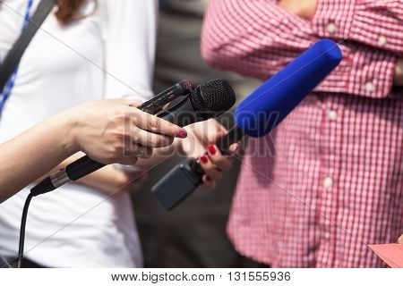 Press interview. Journalists holding a microphone conducting an TV or radio interview.