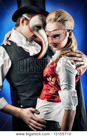 Portrait of the elegant young couple in masquerade costumes. Shot in a studio.