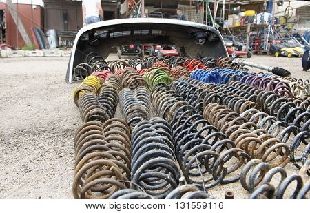 Old used car and trucks springs in a market on a ground