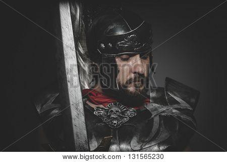 Praetorian Roman legionary and red cloak, armor and sword in war attitude