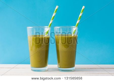 Healthy green detox with spinach, cucumber, lime and apples on blue background