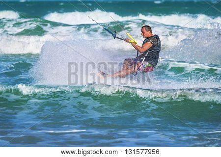 Athletic Man Riding On Kite Surf Board At Sea Waves
