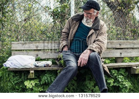 Senior wanderer looking for cigarette lighter. Sitting on bench.