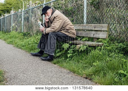 Senior Homeless Man On Bench Holding Bottle.
