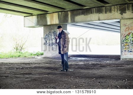 Homeless Senior Man With Bag Standing Under Bridge.