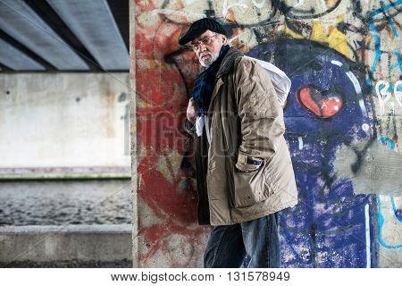 Homeless Man Leaning Against Concrete Pillar Under Bridge.